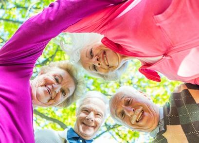 Four elder men and women looking down to camera outdoor. Happine